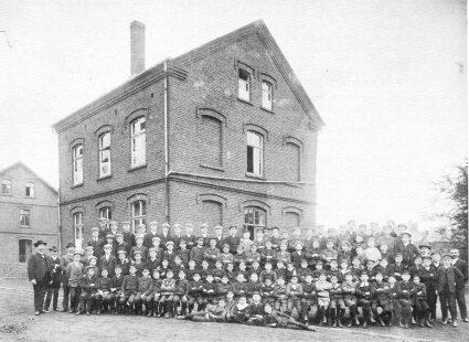 Schülerschaft und Kollegium vor dem Schulgebäude